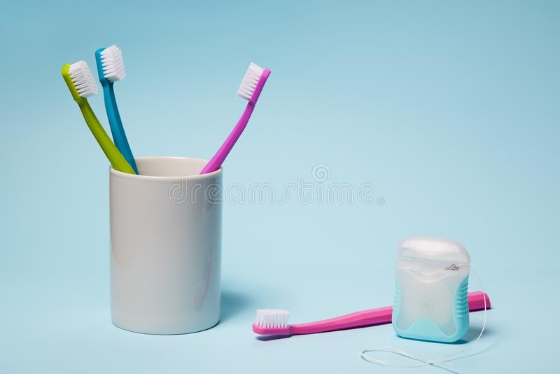 Cepillos de dientes coloridos en taza y seda dental foto de archivo