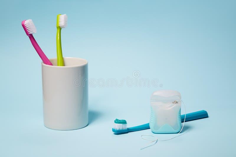 Cepillos de dientes coloridos en taza y seda dental imagen de archivo libre de regalías