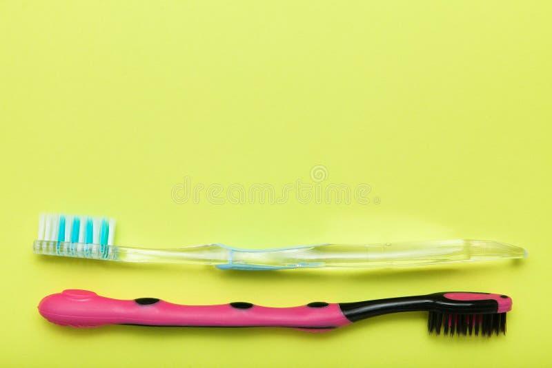 Cepillos de dientes en el fondo amarillo, espacio de la copia imagenes de archivo