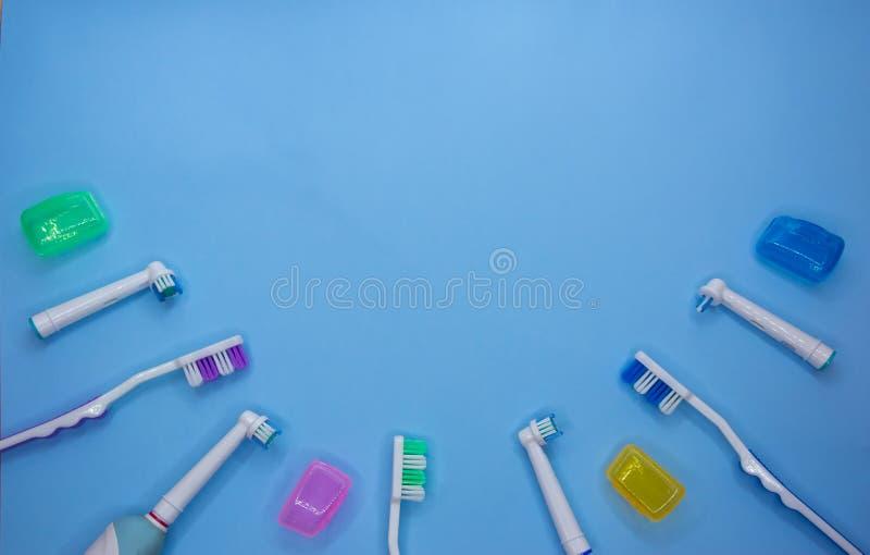 Cepillos de dientes multicolores en un fondo azul con el espacio de la copia imagen de archivo
