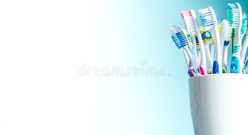 Cepillos de dientes multicolores en un primer blanco de la taza con un fondo de la pendiente del blanco al azul con un lugar aisl imagen de archivo