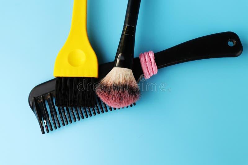 Cepillos de los dos cosméticos y un pequeño peine negro con el elástico rosado del pelo fotografía de archivo libre de regalías
