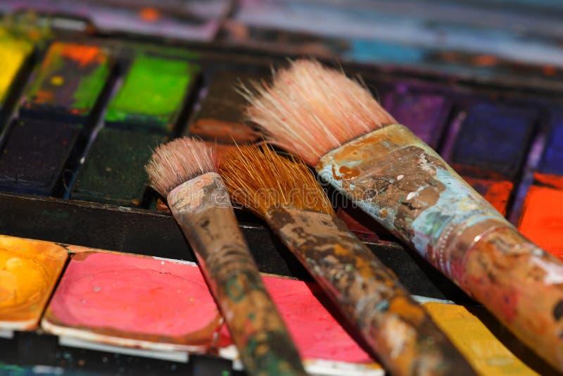 Cepillos de pintura usados en algunas acuarelas fotografía de archivo libre de regalías