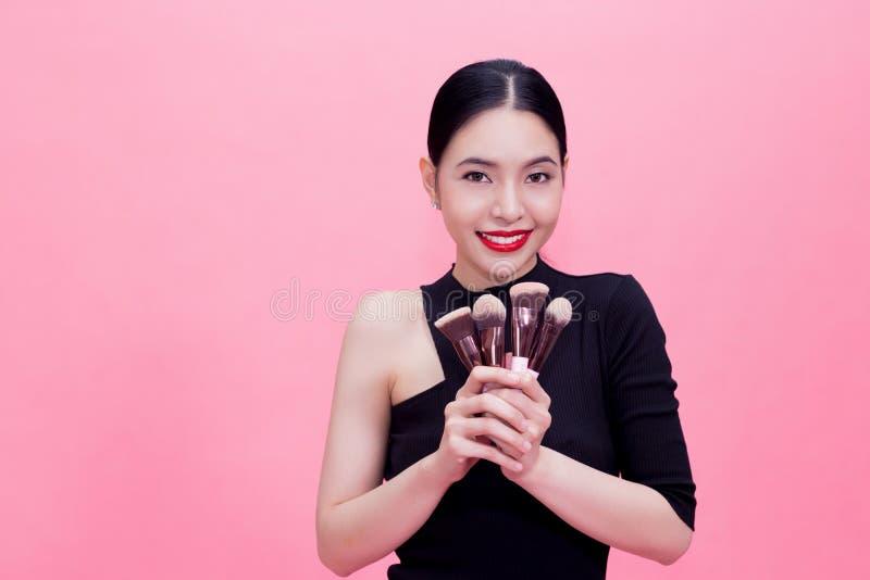 Cepillos del maquillaje de la mujer que llevan asiática elegante joven a mano con c imagen de archivo