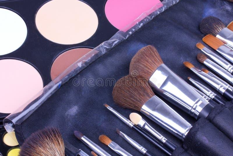 Cepillos del maquillaje en caso de que en las gamas de colores de los sombreadores de ojos fotografía de archivo