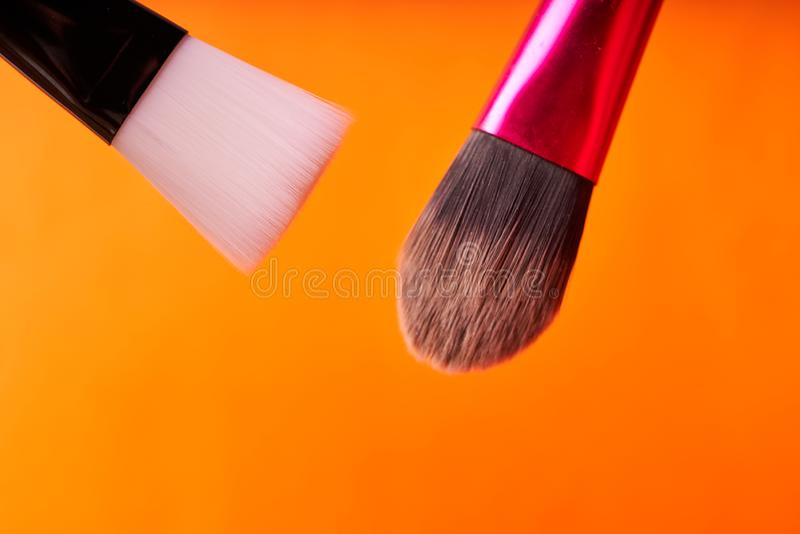 Cepillos del maquillaje en fondo anaranjado Herramientas para los procedimientos cosméticos imagen de archivo