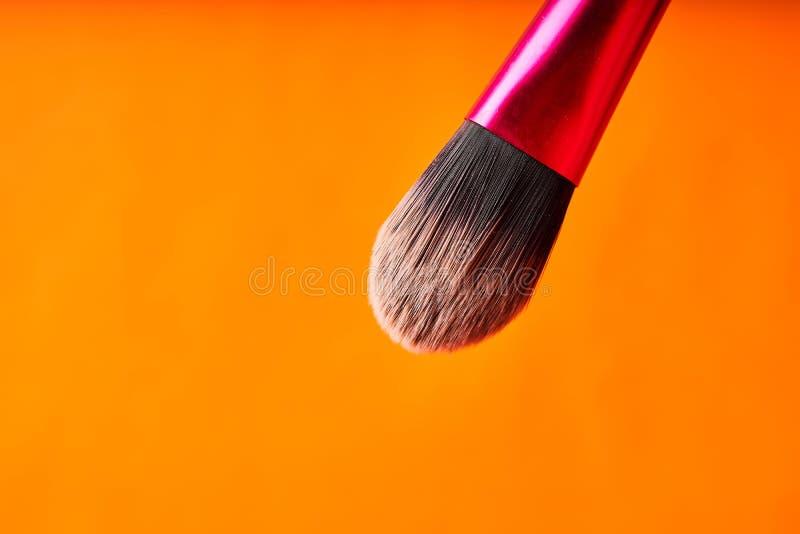 Cepillos del maquillaje en fondo anaranjado Herramientas para los procedimientos cosm?ticos foto de archivo libre de regalías