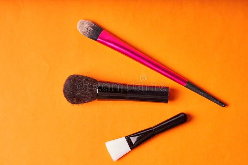 Cepillos del maquillaje en fondo anaranjado Herramientas para los procedimientos cosm?ticos imagen de archivo libre de regalías