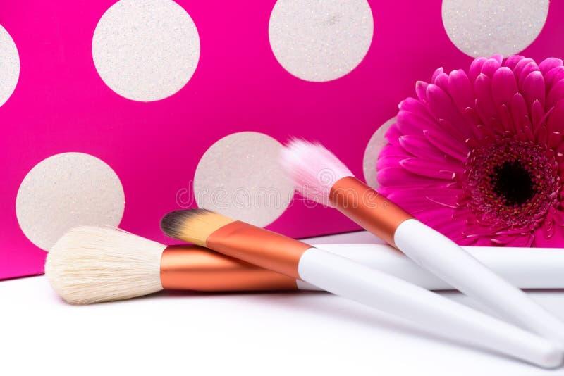 Cepillos del maquillaje en fondo rosado de los lunares. fotos de archivo libres de regalías