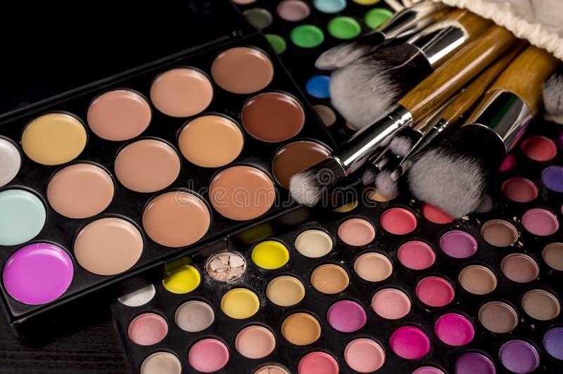 Cepillos del maquillaje en las paletas del maquillaje foto de archivo libre de regalías