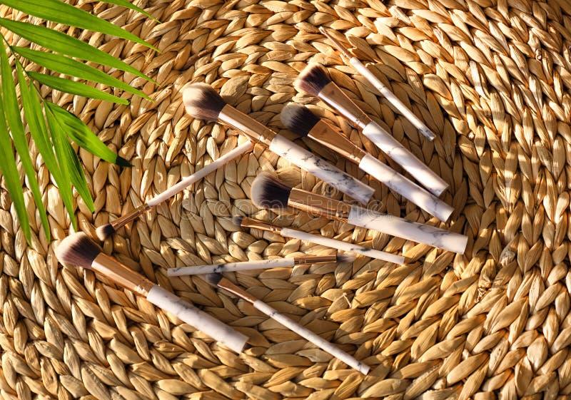Cepillos del maquillaje para aplicar los cosméticos decorativos en la estera de mimbre foto de archivo libre de regalías