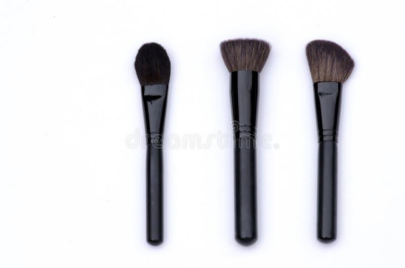 Cepillos determinados del profesional para el maquillaje de la cara en fondo negro, blanco imágenes de archivo libres de regalías