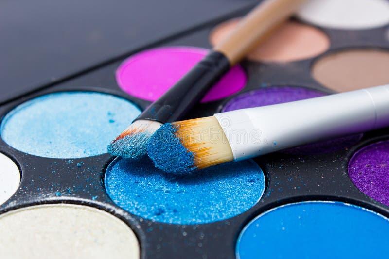 Cepillos para el maquillaje en las paletas de la sombra de ojos fotos de archivo libres de regalías