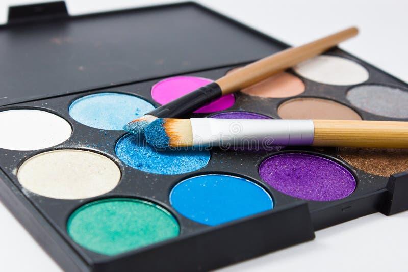 Cepillos para el maquillaje en las paletas de la sombra de ojos fotos de archivo