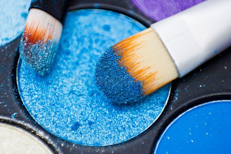 Cepillos para el maquillaje en las paletas de la sombra de ojos imagen de archivo