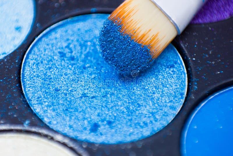 Cepillos para el maquillaje en las paletas de la sombra de ojos fotografía de archivo