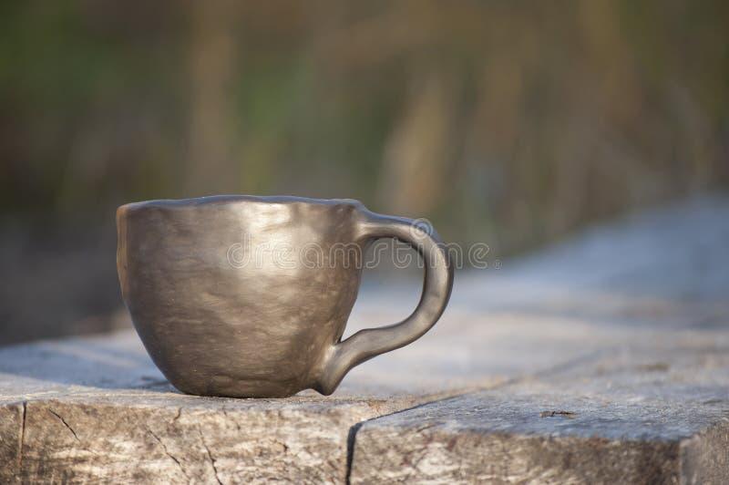 Cerâmica preta Humor da manhã com o close up bonito da caneca feito a mão original na luz solar imagens de stock royalty free