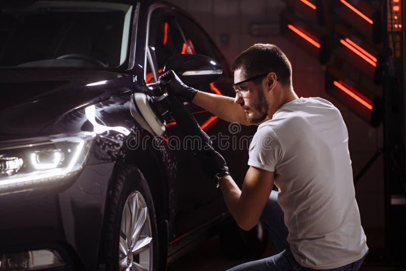 Cera del pulimento del coche manos del trabajador que sostienen un pulidor fotografía de archivo