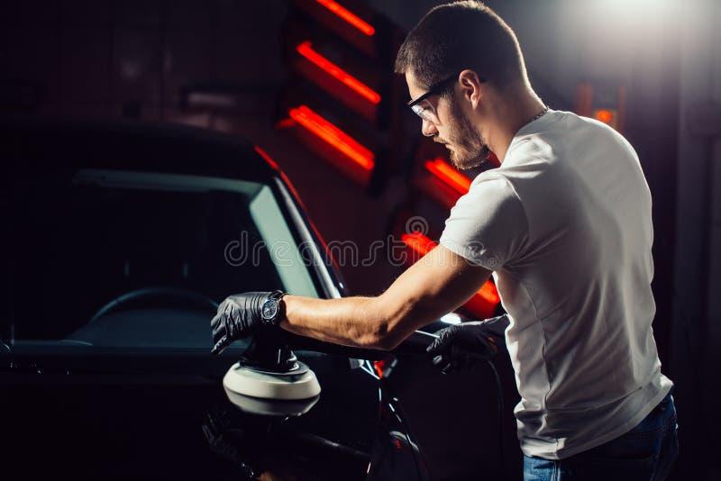 Cera della lucidatura dell'automobile il lavoratore passa la tenuta del lucidatore fotografia stock