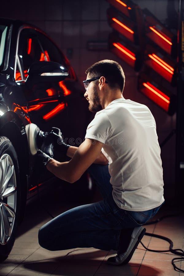 Cera do polimento do carro mãos do trabalhador que guardam um polisher imagens de stock royalty free