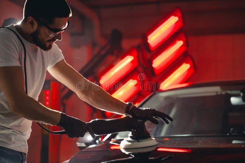 Cera do polimento do carro mãos do trabalhador que guardam um polisher imagem de stock royalty free