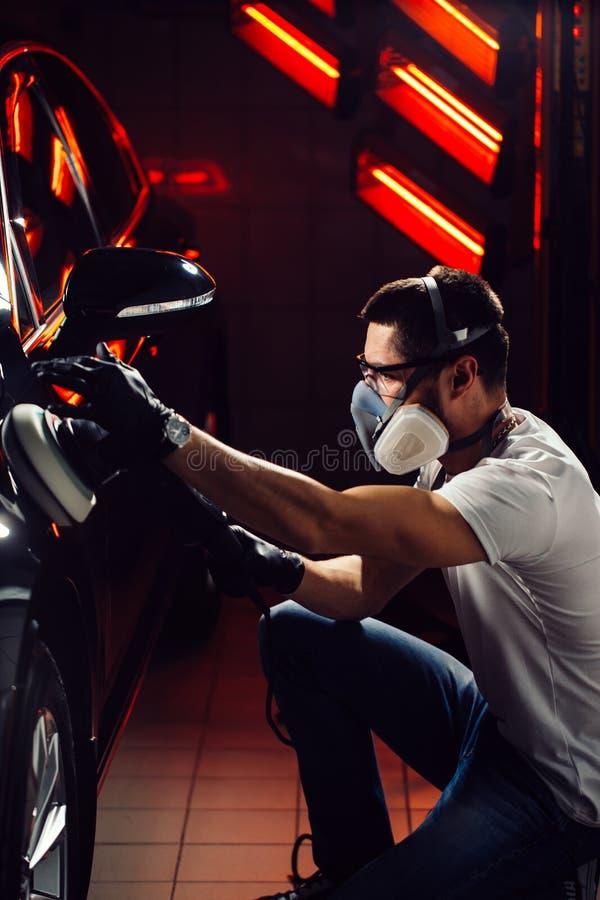 Cera do polimento do carro mãos do trabalhador que guardam um polisher imagem de stock