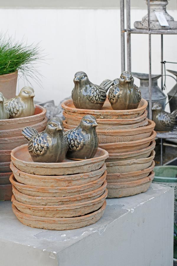 Ceramic birds and old dishes from flower pots stock photo