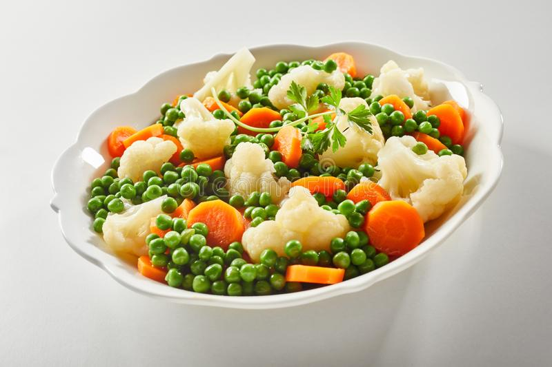 Ceramic bowl of tender steamed mixed vegetables royalty free stock images