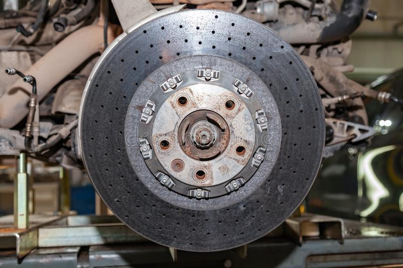 Ceramic brake disc from a perforated vehicle with a floating mounting system mounted on the hub of the vehicle during an upgrade royalty free stock image