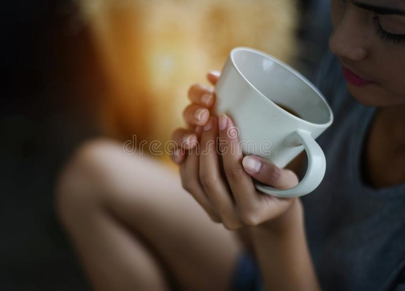 The ceramic coffee cup was holding by lady hand,warm light tone stock photos
