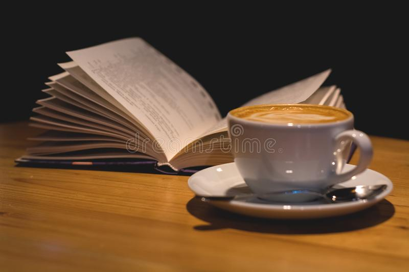 Ceramic cup of cappuccino in coffee shop with pattern on a wooden table with an open book. Latte art. Morning drink. Caffeine. stock image