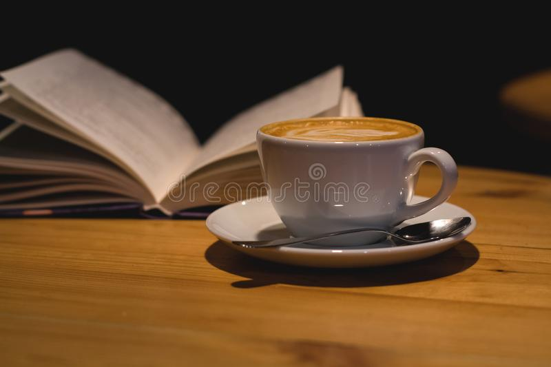 Ceramic cup of cappuccino in coffee shop with pattern on a wooden table with an open book. Latte art. Morning drink. Caffeine. stock photography