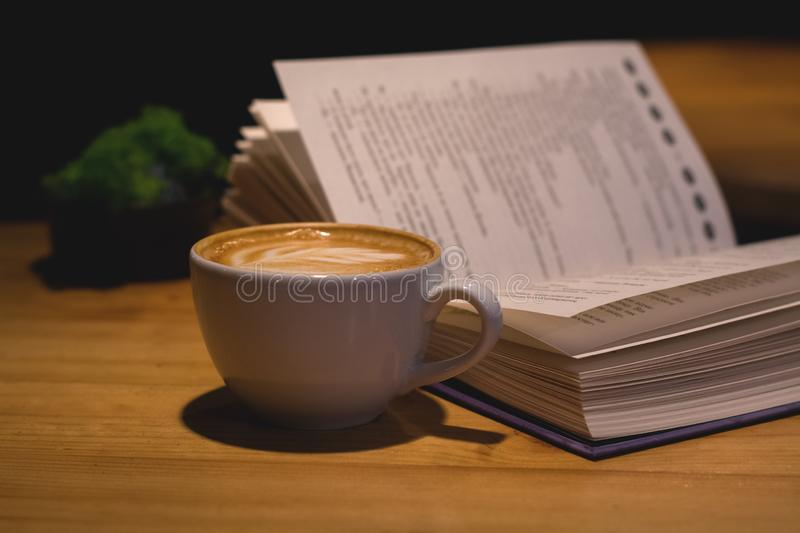 Ceramic cup of cappuccino in coffee shop with pattern on a wooden table with an open book. Latte art. Morning drink. Caffeine. stock photos