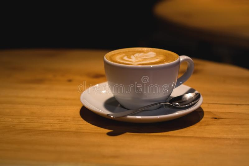 Ceramic cup in coffee shop with cappuccino on wooden empty table. Latte art. Morning drink. Caffeine. royalty free stock photography