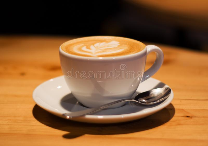 Ceramic cup in coffee shop with cappuccino on wooden empty table. Latte art. Morning drink. Caffeine. royalty free stock photo