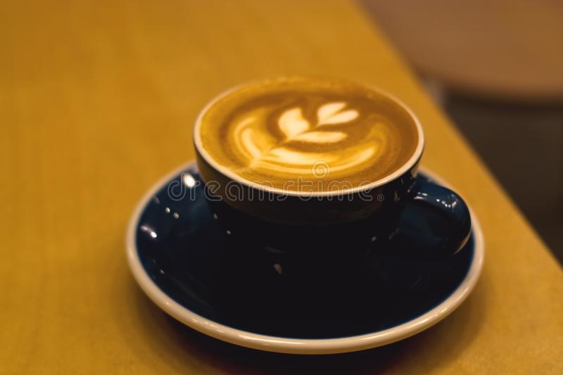 Ceramic cup in coffee shop with cappuccino on wooden empty table. Latte art. Morning drink. Caffeine. stock photos