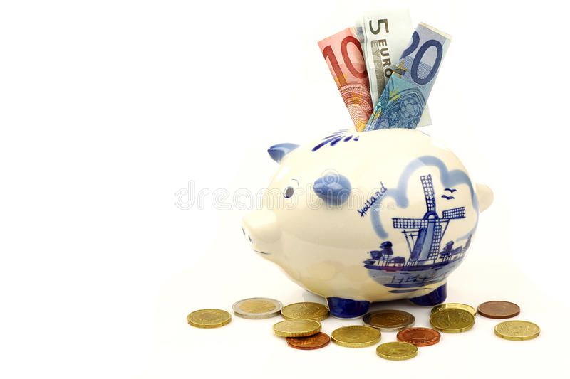 Ceramic Delft Blue piggy bank with euro paper money. And coins on a white background stock photography