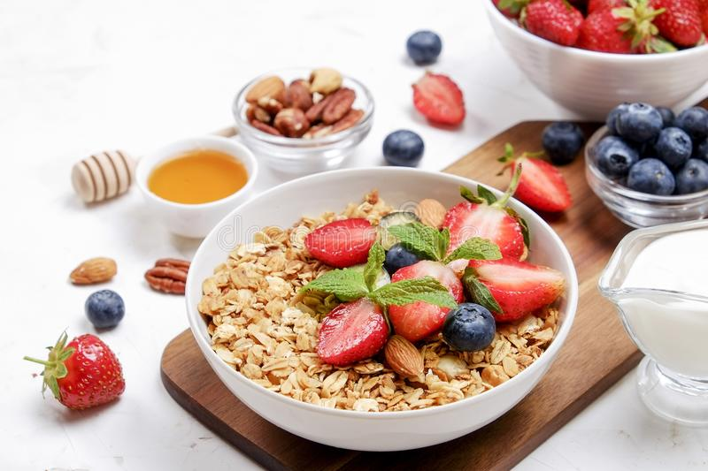 Ceramic granola bowl, assorted ingredients on table. Healthy nutritious breakfast with vegan yogurt, raw fruits, nuts and cereals. stock images