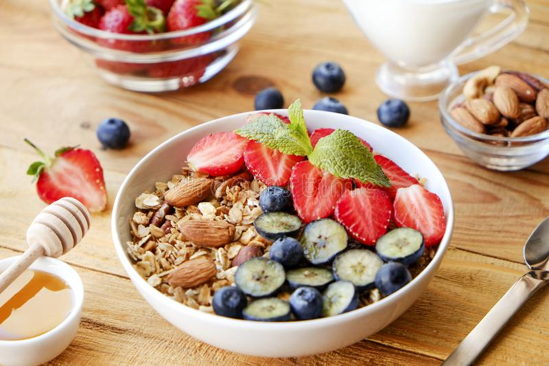 Ceramic granola bowl, assorted ingredients on table. Healthy nutritious breakfast with vegan yogurt, raw fruits, nuts and cereals. royalty free stock photos