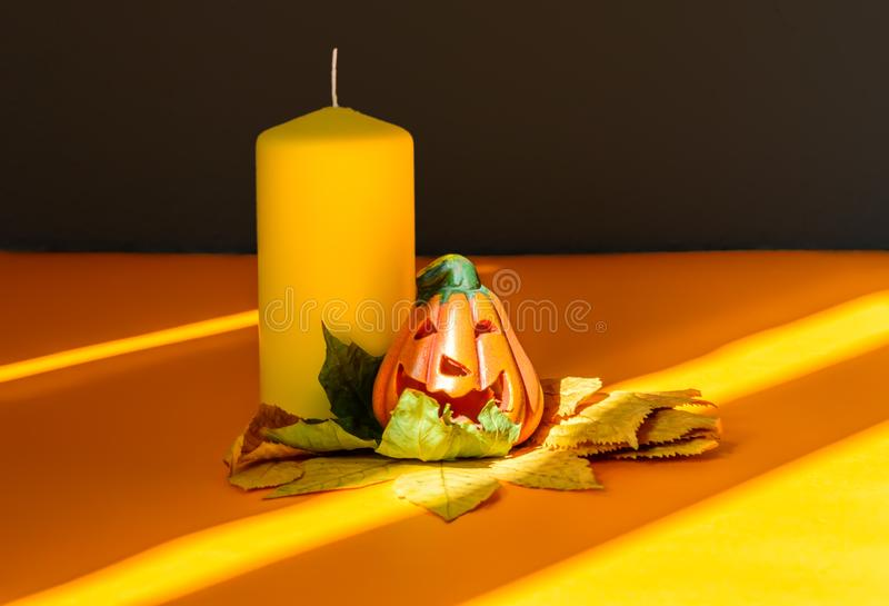 Ceramic Halloween pumpkin jack-o-lantern on dry autumn leaves, yellow candle and strong shadows stock photo