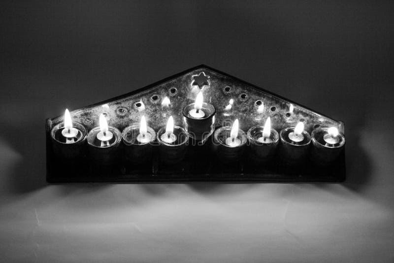 Ceramic hanukiah lit with 4 candles and shamash b&w, top view royalty free stock photo