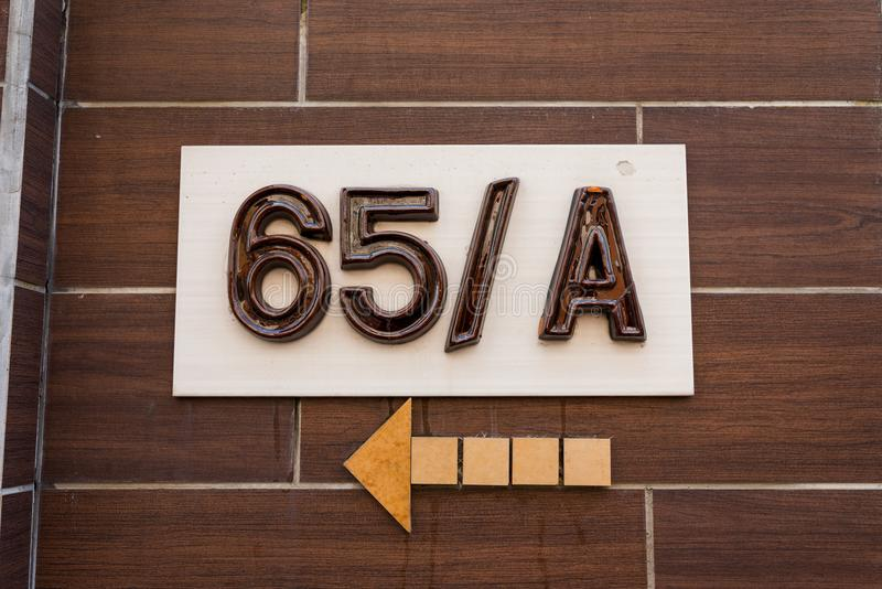 Ceramic house number on the wall and arrow direction royalty free stock photography