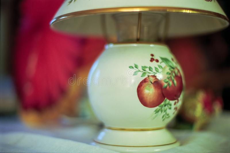 A Ceramic Lamp with a Painting of Apples on it stock image