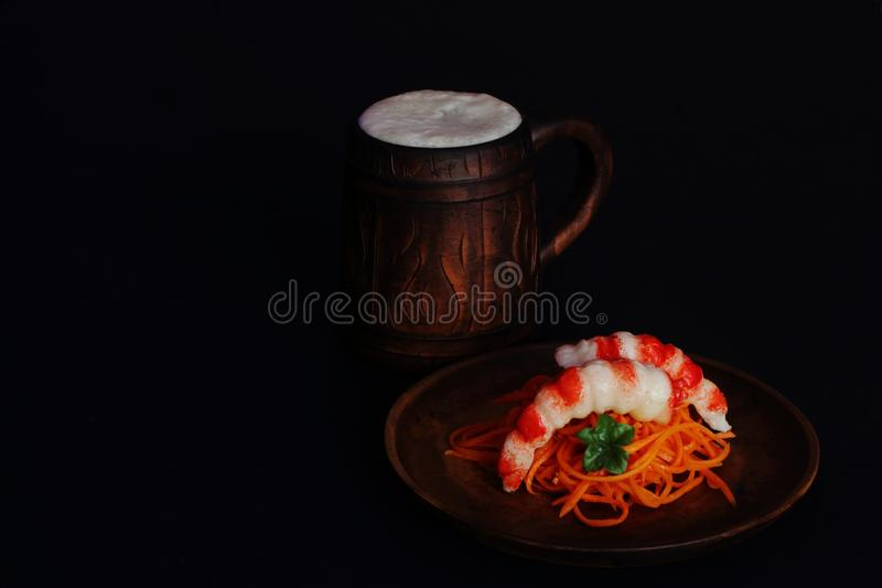 Ceramic mug with beer and clay plate with appetizing shrimps and spicy pickled carrots on black background. Concept — delicacies stock photos