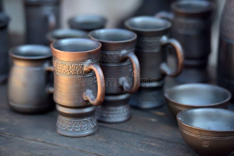 Ceramic mugs and bowls. Of dark clay royalty free stock photos