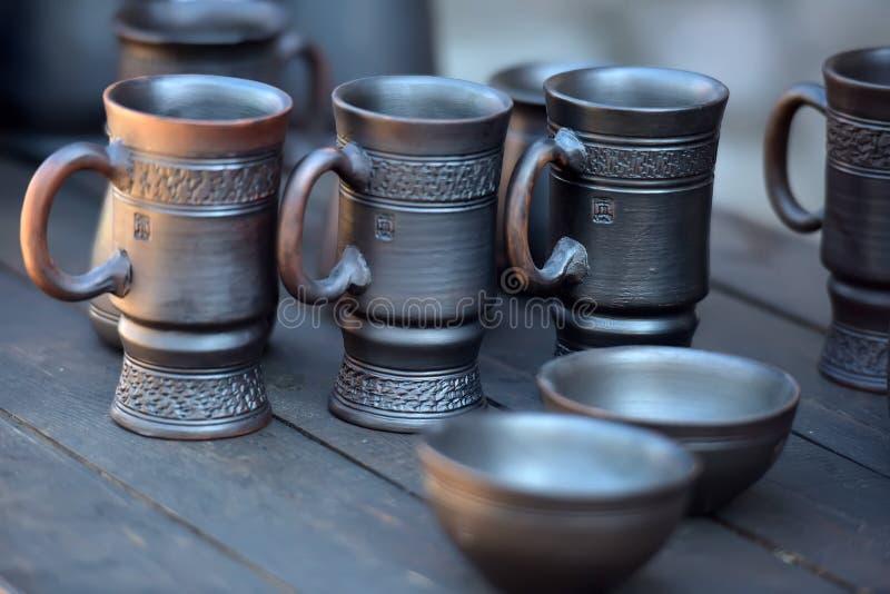 Ceramic mugs and bowls. Of dark clay stock photo