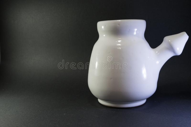 Ceramic neti pot used for irrigating nasal passages. Device for washing the nose. Om symbol in jug. Jar to clean sinusitis. Background, salt, saline, treatment stock photo