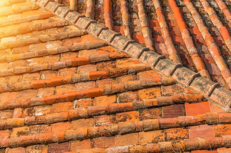 Ceramic orange clay tiles on the roof of a building, corner sunlight glare.  royalty free stock image