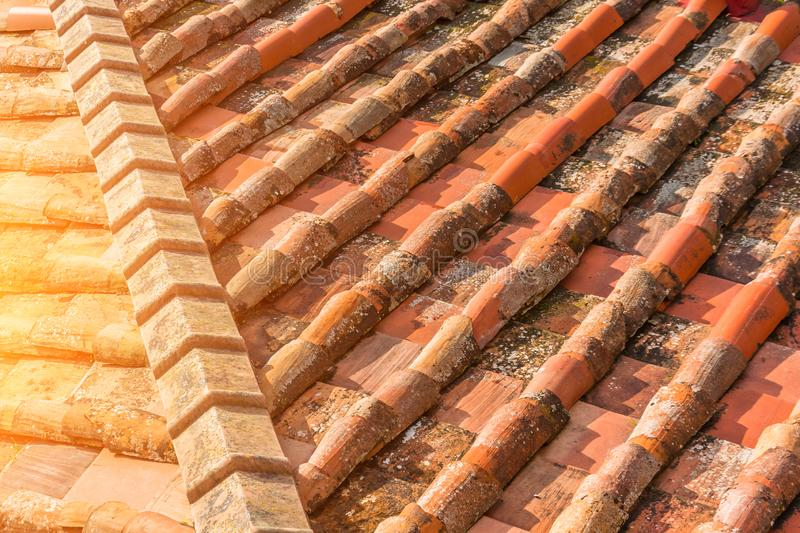Ceramic orange clay tiles on the roof of a building, corner sunlight glare.  royalty free stock photo