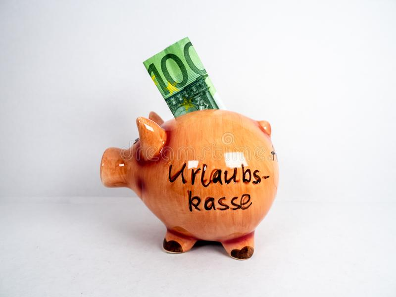 Ceramic piggy bank with Euro inside saved up for holiday. Single cute ceramic piggy bank with 100 Euro bill partially stuck inside of it saved up for holiday on stock image
